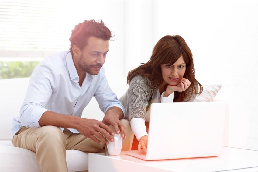 couple à la recherche à l'ordinateur portable