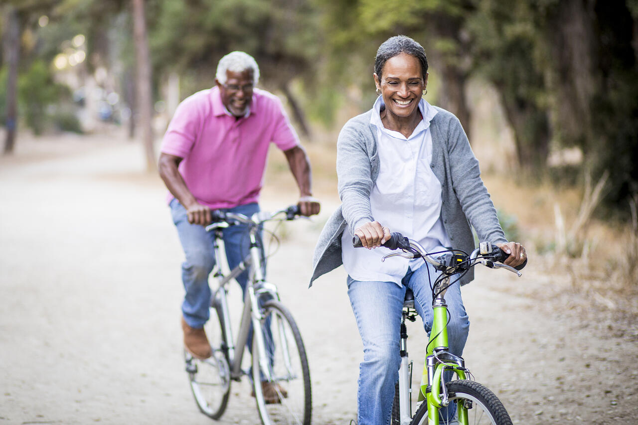Smiling senior couple riding bicycles on a nature trail