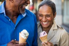 Smiling senior couple eating ice cream on a cone