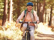 Smiling senior woman mountain biking in the forest
