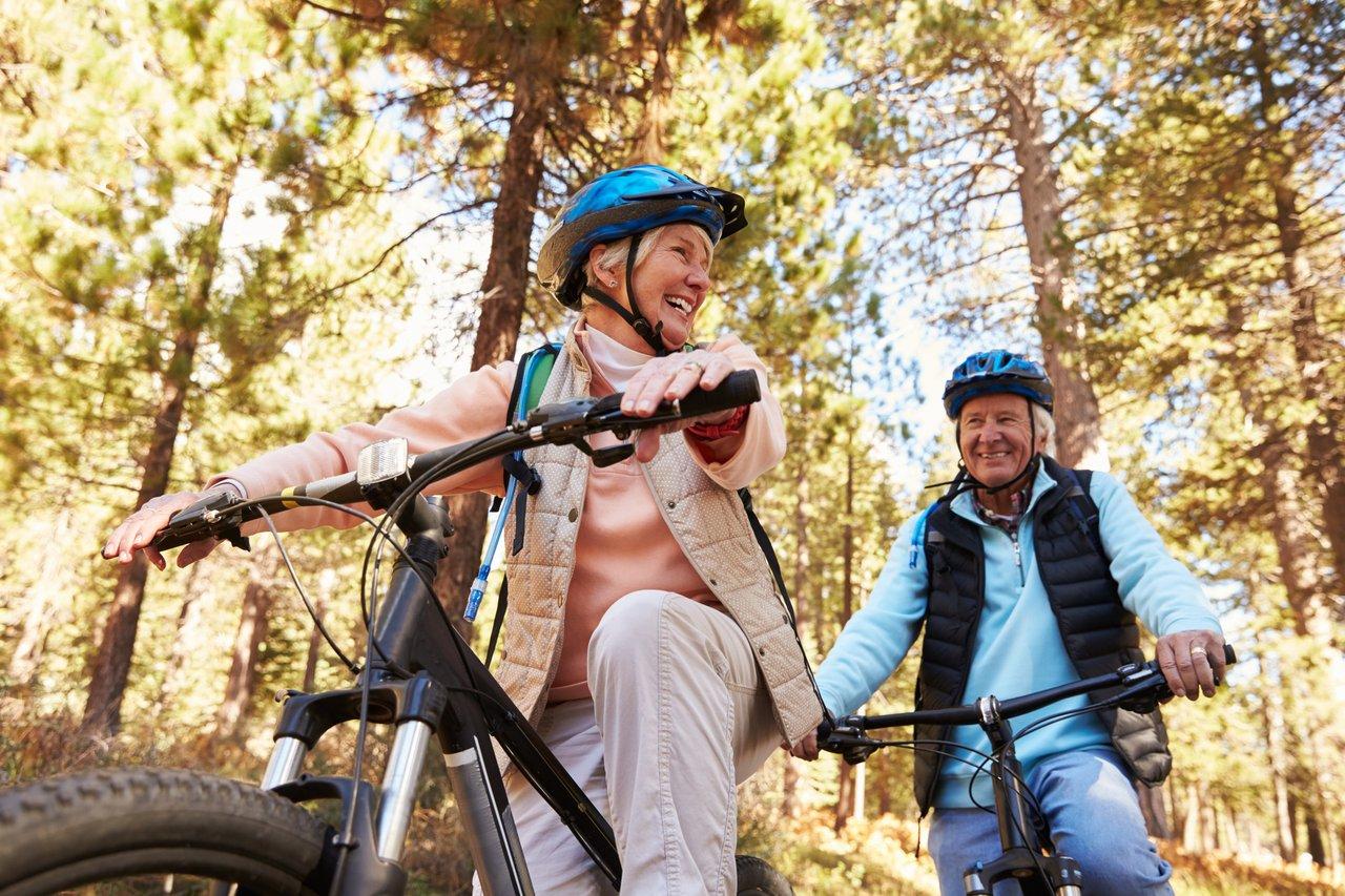 Smiling senior couple mountain biking on a forest trail