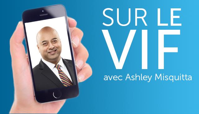 Main qui tient un cellulaire affichant le visage d'un homme d'affaires à côté du texte « Sur le vif avec Ashley Misquitta »