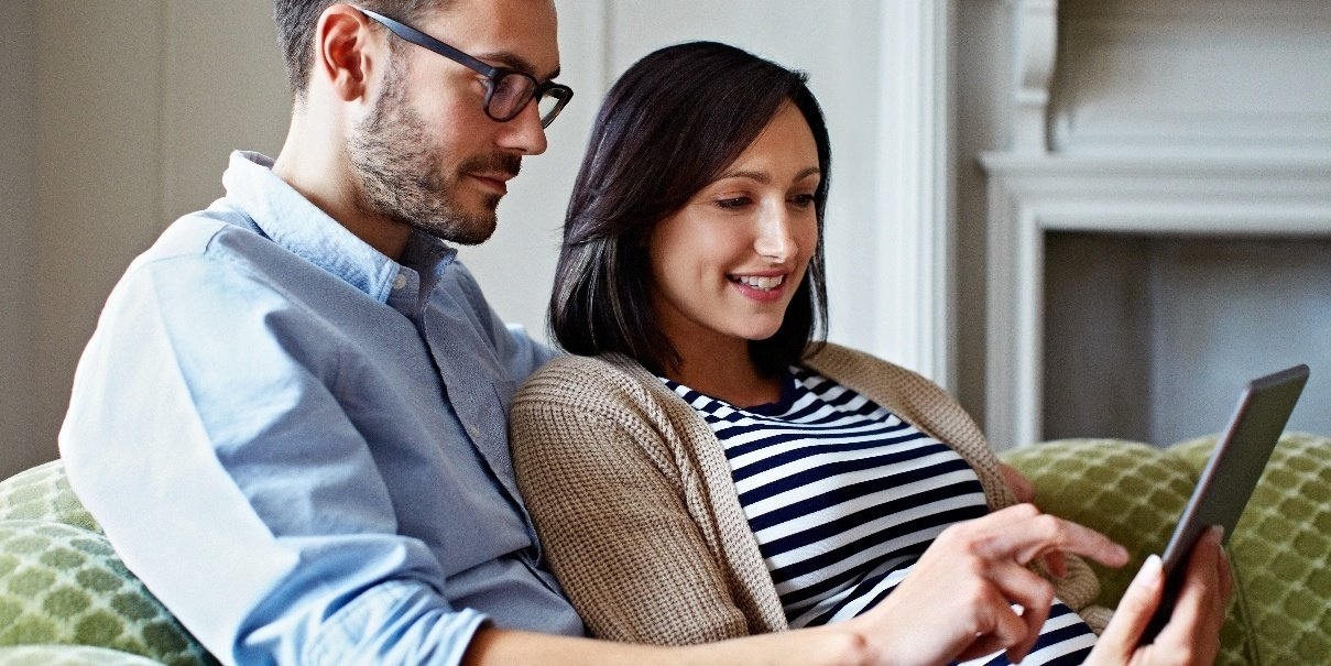 Young man and expecting woman looking at tablet